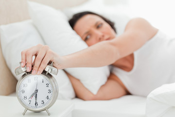 Alarm clock being turned off by a woman