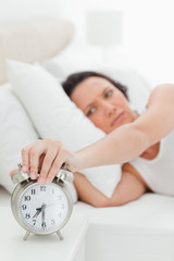 Close-up of an alarm clock being turned off by a woman