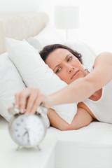 Close-up of woman in her bed turning off her alarm clock