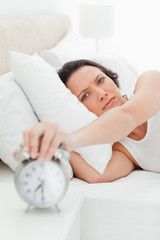 Close-up of a young woman in her bed turning off her alarm clock