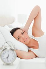 Woman hands over  her ears in  bed