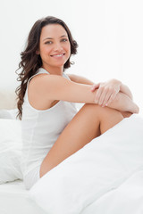 Close-up of a smiling woman sitting in her bed