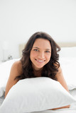 Close-up of a happy young brunette in her bed