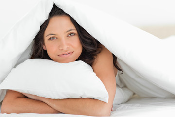 Smiling woman hugging a pillow