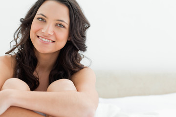 Close-up of a smiling young brunette sitting in her bed