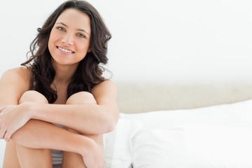 Smiling young brunette sitting in her bed
