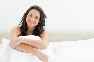 Smiling attractive brunette sitting in her bed