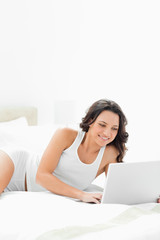 Close-up of an attractive brunette lying on her bed with a laptop