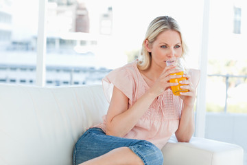 Woman lying on a sofa while drinking an orange juice