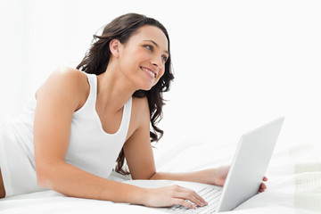 Young woman with her laptop on her bed