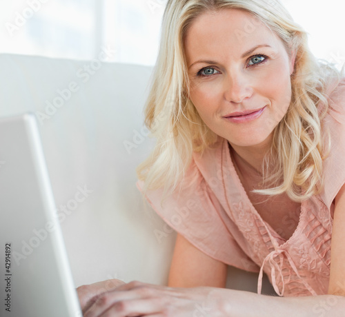 Close-up of a woman in pink shirt tapping on her laptop