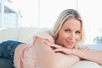 European woman smiling while lying on her sofa