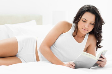 Attractive woman reading a book on her bed