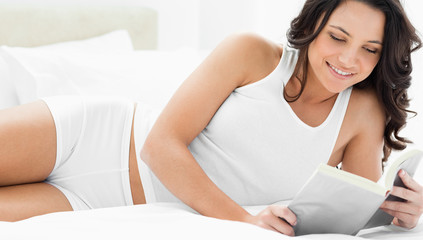 Pretty woman reading a book on her bed