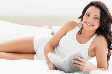 Brunette reading a book on her bed
