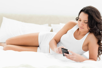 Attractive woman texting on her bed