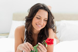 Beautiful young woman holding a rose