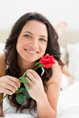 Smiling pretty woman holding a rose