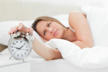Sleepy woman turning off her alarm