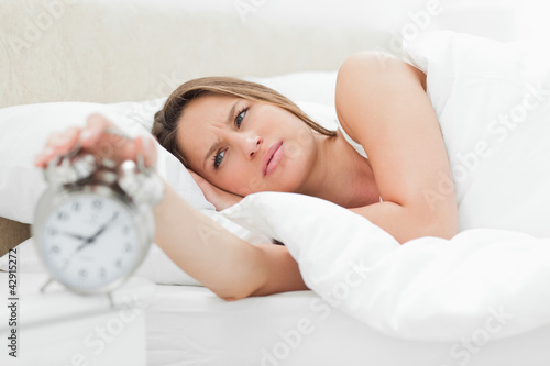 Young woman turning off her alarm