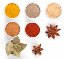 Different spices in white bowls isolated on white background.