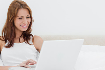 Redheaded woman smiling while using a personal computer