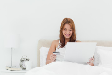 Smiling redheaded using her credit card online