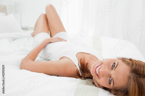 Portrait of an attractive woman smiling while lying on her back