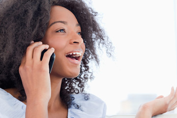 Close-up of a fuzzy hair woman talking on the phone