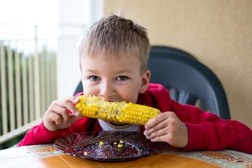 Сhild eats corn
