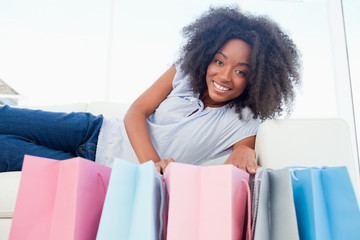 Portrait of a smiling fuzzy hair woman looking into her shopping bags