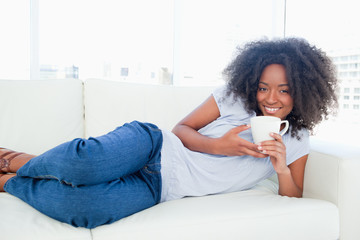 Portrait of a fuzzy hair woman drinking a tea