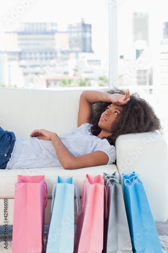 Close-up of an exhausted woman lying on her sofa