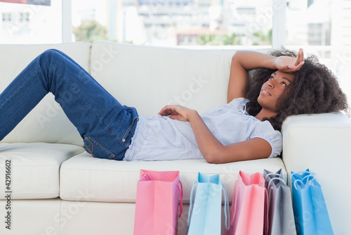 Exhausted woman lying on her sofa