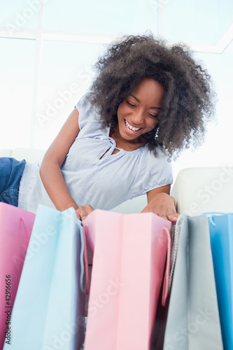 Laughing fuzzy hair woman looking into her shopping bags