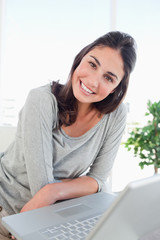 Portrait of a beaming woman using a personal computer