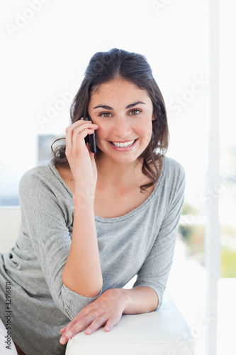 Portrait of a smiling young woman phoning