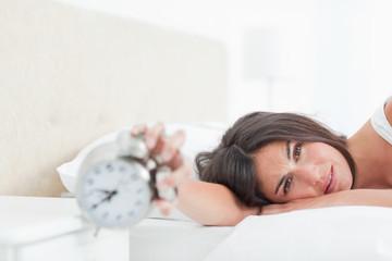Sad brunette turning off her alarm