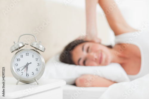 Brunette waking up by her alarm ringing