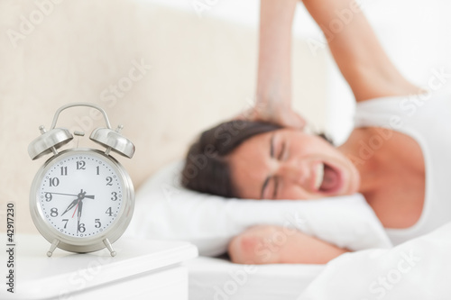 Upset brunette waking up by her alarm
