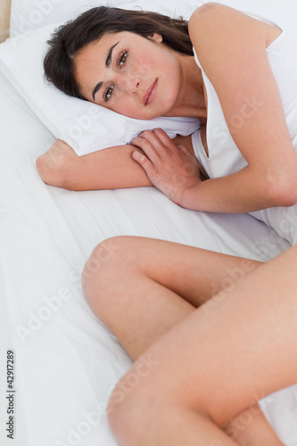 Close-up of a brunette lying on her bed
