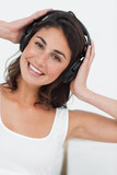 Portrait of a smiling brunette listening to music