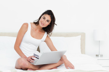 Portrait of an attractive brunette, a laptop on knees shopping online