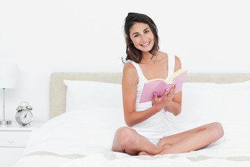Portrait of a brunette with cross-legged reading a book
