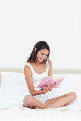Smiling brunette cross-legged reading a book