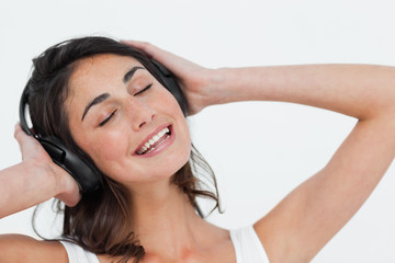 Close-up of a happy brunette listening to music