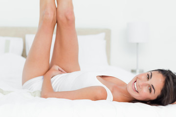 Portrait of a smiling brunette playing on her bed