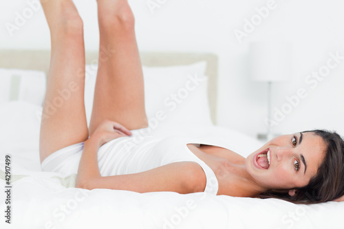 Portrait of a brunette playing in her bed