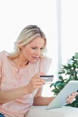Blonde buying online with a touchpad