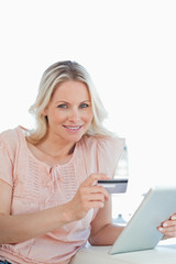 Portrait of a blonde buying online with a touchpad